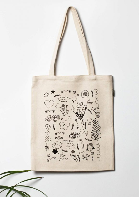 Cotton tote bag with black print with flowers, lips, eyes, hands, fruits, faces, placed in a shape of a rectangle.