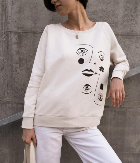 A girl with a beige cotton sweatshirt with black print of eyes & lips.