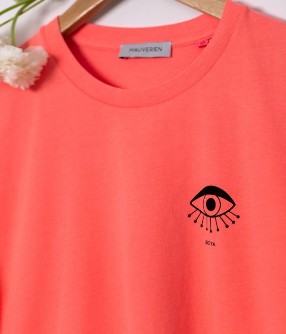 Close-up of neon pink t-shirt with black print of a minimalist eye.