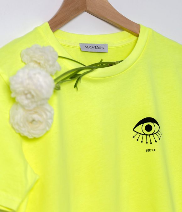 Close-up of a neon yellow t-shirt with black print of an eye and see ya message printed on the top left of the chest.