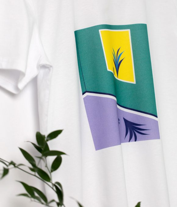 Detail of a white cotton t-shirt with print in purple, green & yellow with plants placed in a rectangle.