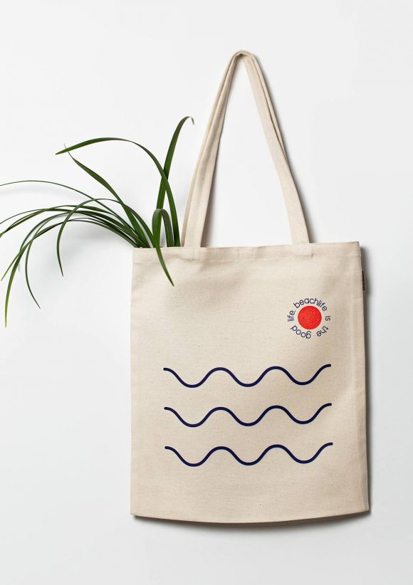 Beige cotton tote bag with three wavy bluemarine lines placed horizontally and writing around a small orange circle.
