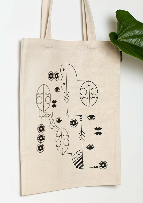 Close-up of the black print of the Faces cotton tote bag, with three faces and floral motifs.