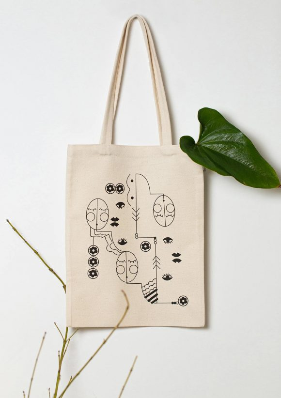Organic cotton tote bag with print on all surface, representing three faces and floral motifs.
